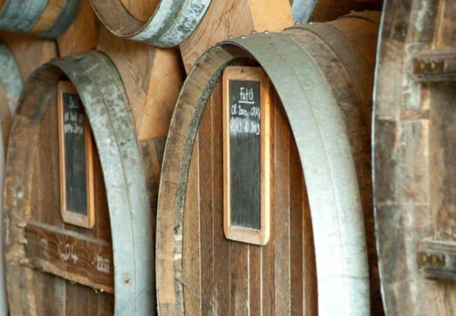 Tonneaux et fûts de calvados dans le chai de vieillissement d'une distillerie du Calvados