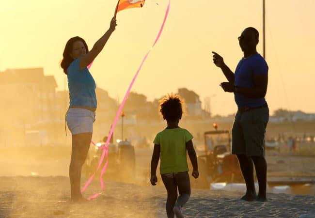 Une famille au coucher du soleil sur la plage qui jour au cerf-volant