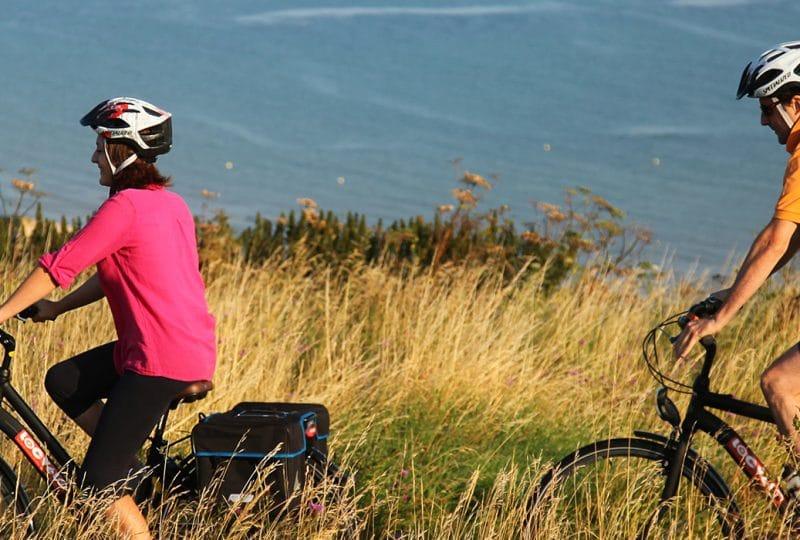 Couple en balade à vélo le long du littoral