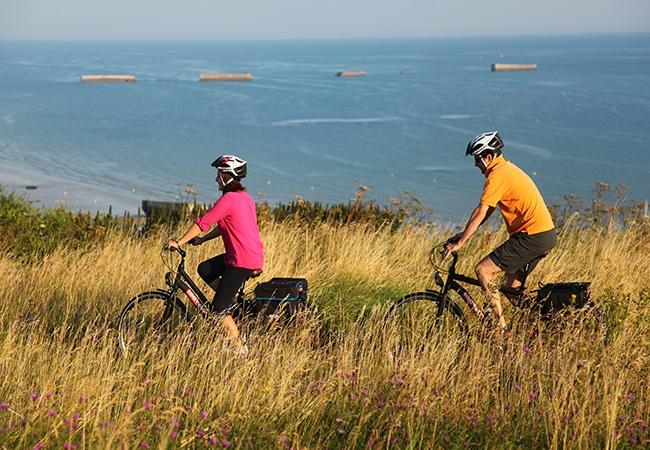 Couple en balade à vélo le long du littoral du Calvados en Normandie