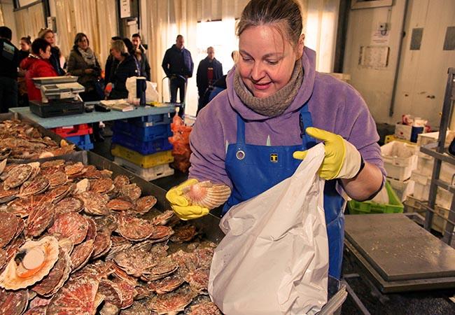 Femme vendant des coquilles saint jacques sur un marché du Calvados en Normandie