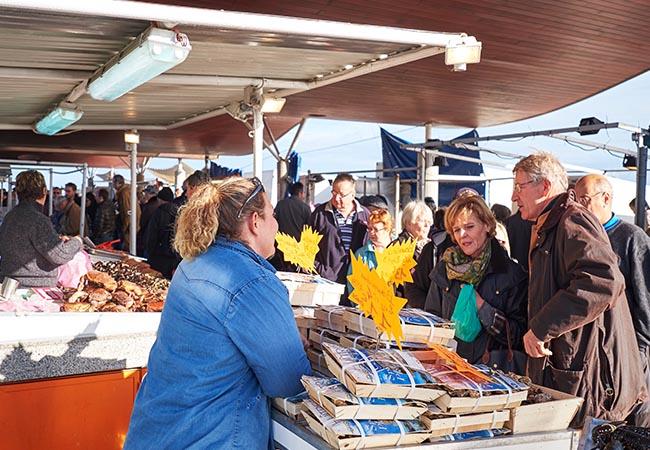 Personnes achetant du poisson sur un marché du Calvados