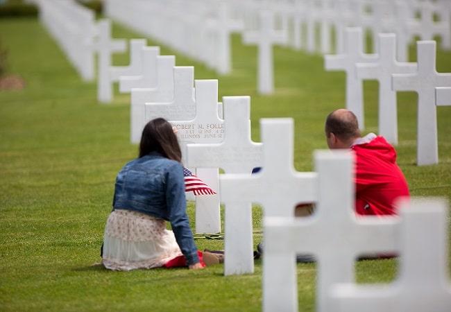 Personnages se recueillant devant des croix au cimetière américain de Colleville sur Mer