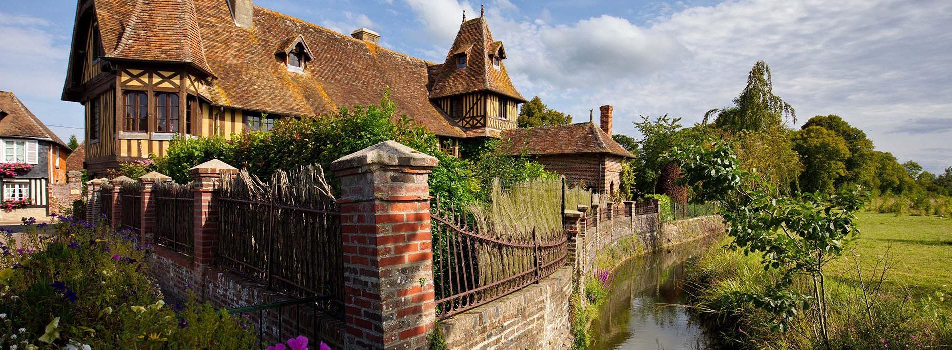 Maison en colombage dans le Calvados en Normandie, bordée d'un ruisseau