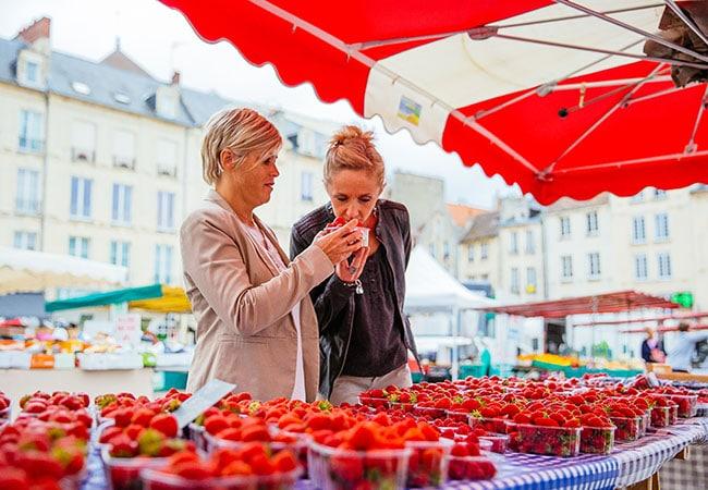 Femmes sentant les fraises au marché de Caen dans le Calvados