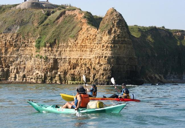 Kayak au pied de la Pointe du Hoc, site des plages du débaruqement dans le Calvados en Normandie