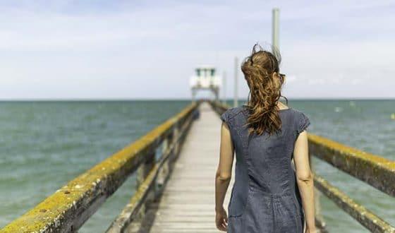 Femme marchant sur la jetée à Luc-sur-mer