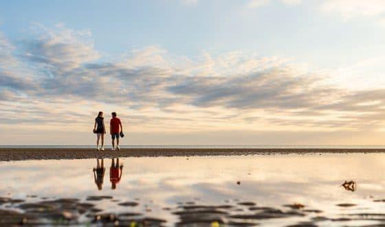 Couple se baladant sur la plage au coucher du soleil