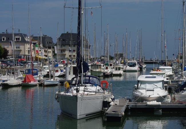 Voiliers et bateaux moteur aux pontons dans un port de plaisance du Calvados