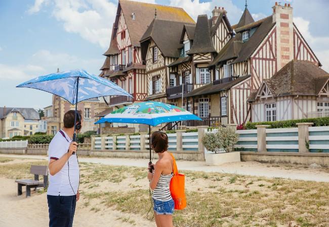 personnages avec ombrelles connectées devant des villas de la côte de nacre