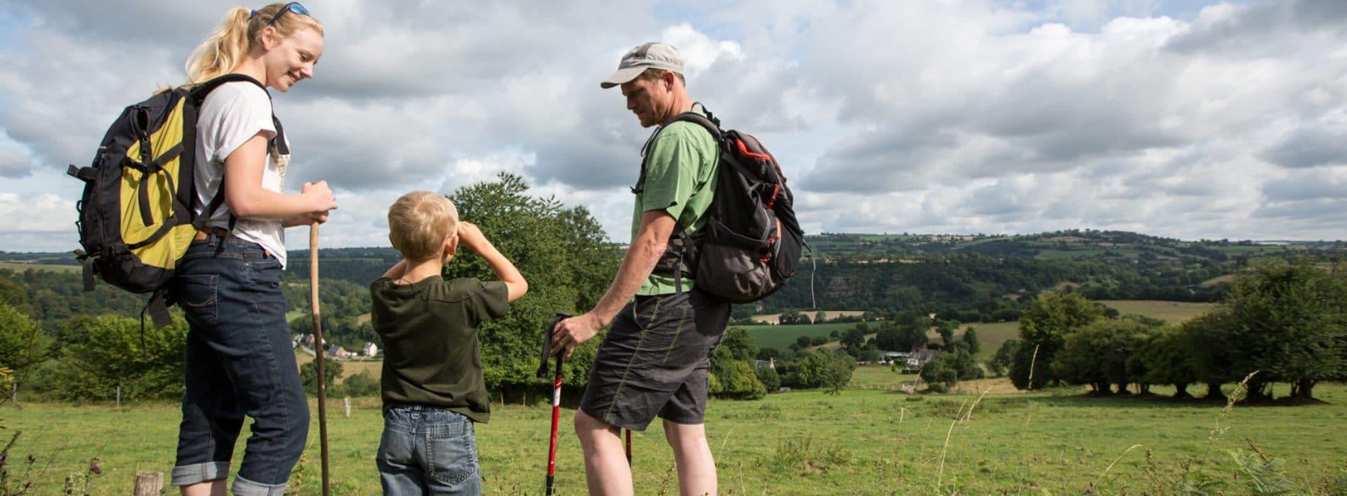 couple avec enfant en randonné pédestre dans des champs