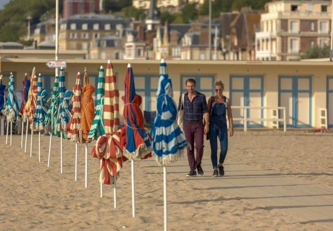 Un couple se promène sur la plage de Trouville-sur-Mer