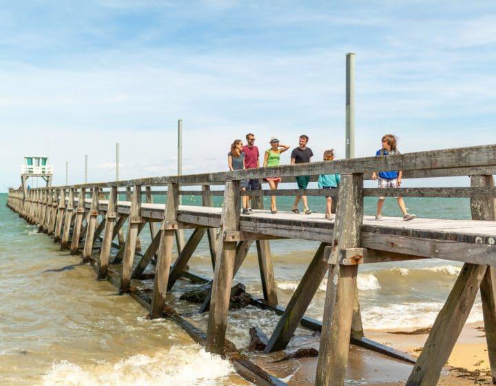 promeneurs sur la jetée de Luc-sur-mer (Calvados)