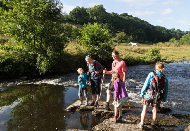 couple avec enfants en randonnée pédestre au bord d'une rivière bordée de champs