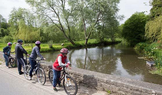Famille en balade à vélo le long d'un cours d'eau
