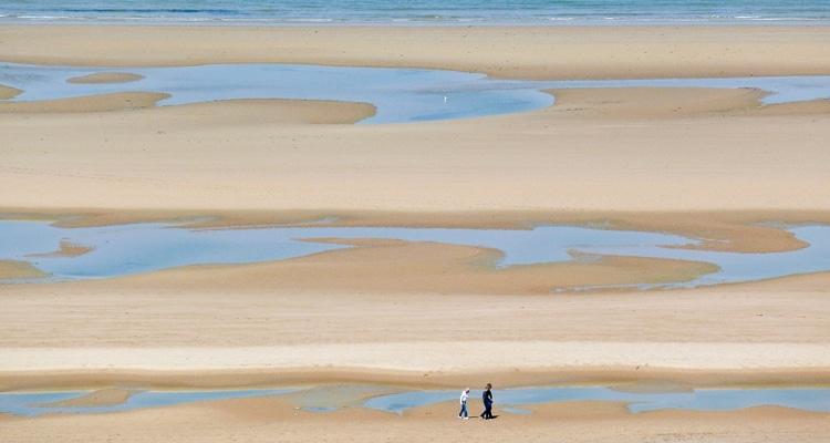 Personne se baladant sur la plage à marée basse