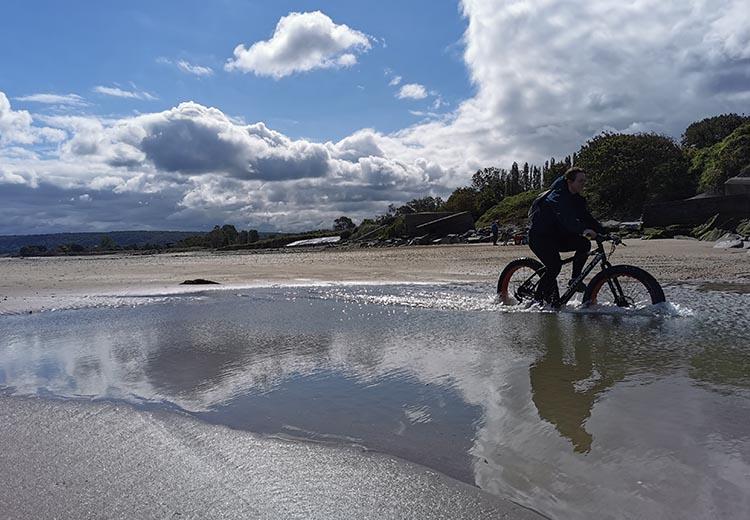 Femme faisant du fatbike sur la plage