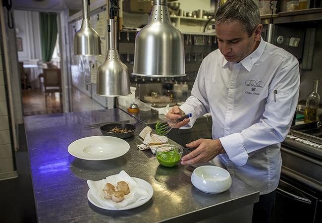 Chef cuisinier dans sa cuisine préparant une recette
