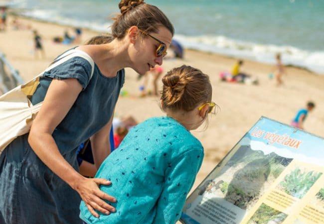 Une mère et ses enfants au bord de la plage lisant des informations