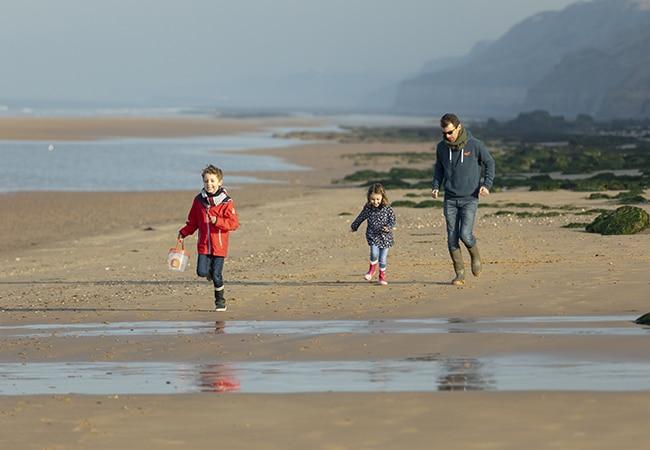 Un père et ses enfants courant sur la plage