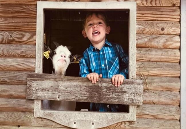 Enfant et chèvre dans maison en bois