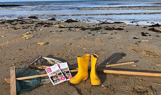 Des bottes et des épuisettes sur le sable à la plage
