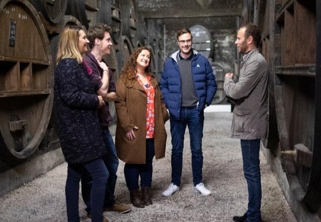visiteurs découvrant les chais de la distillerie des calvados Roger Groult