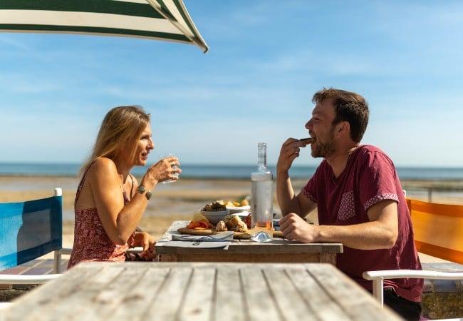 jeune couple mangeant des fruits de mer dans un restaurant au bord de la mer en Normandie