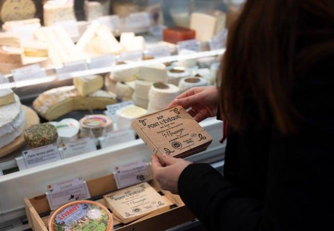 personne achetant un fromage normand sur un marché à Caen
