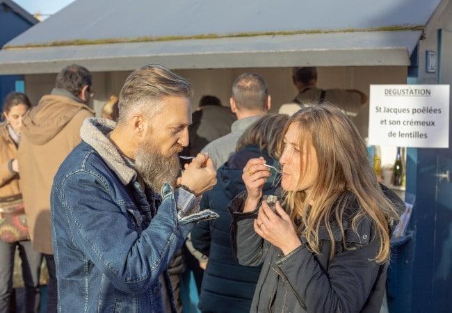 couple dégustant une soupe de poissons sur le port pendant la fête de la coquille Le goût du Large à Port en Bessin