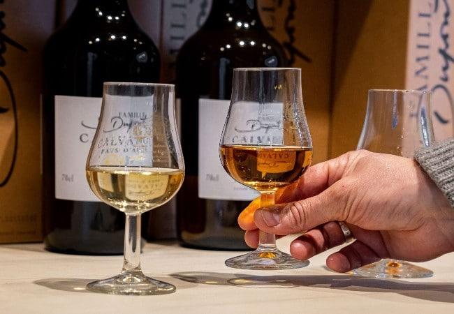 verres de calvados devant bouteilles de calvados et main tenant un verre de calvados hors d'âge