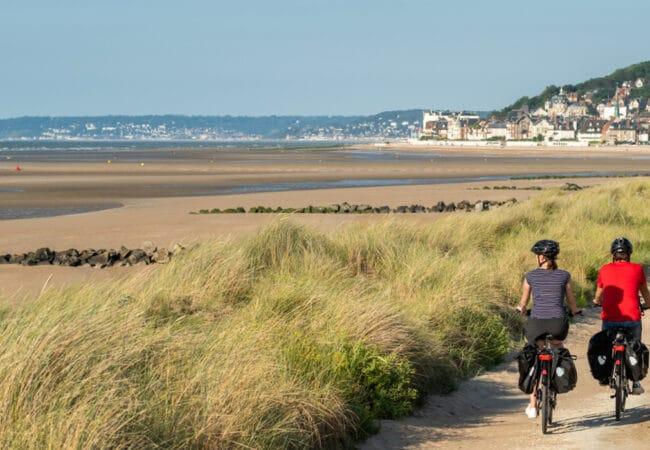 Balade en couple à vélo dans les dunes le long de la mer