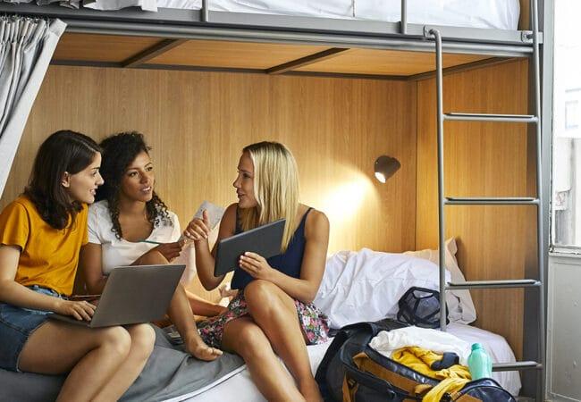 Jeunes femmes assises sur un lit superposé préparant leur journée de voyage