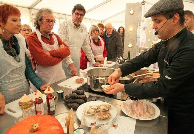 chef faisant une démonstration de cuisine de coquilles saint jacques devant du public pendant la fête de la coquille
