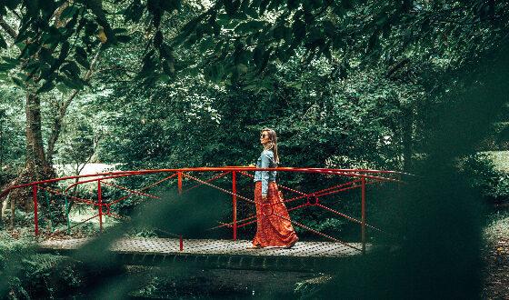 Une femme marche sur un pont rouge dans un parc