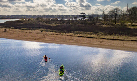 Deux kayaks en mer dans la baie de l'Orne avec une vue sur l'observatoire de Ouistreham