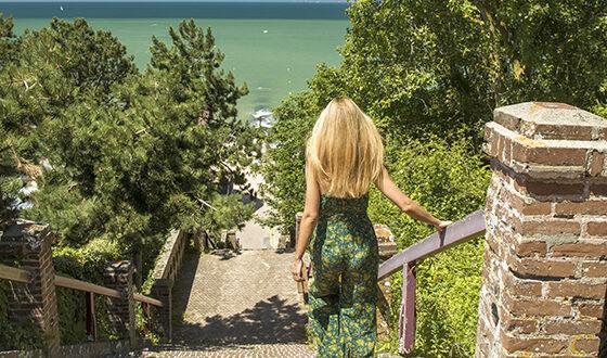 Femme descendant des escaliers menant à la mer