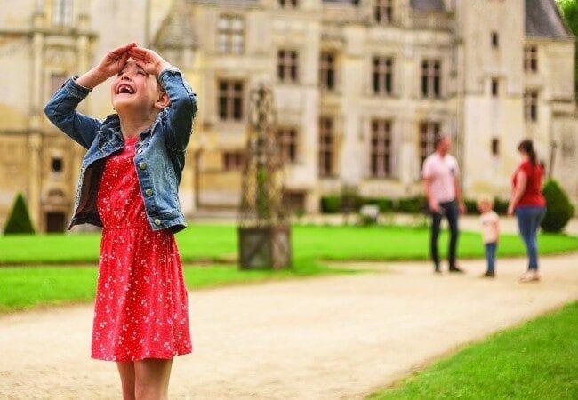 petite fille regardant en l'air devant un château