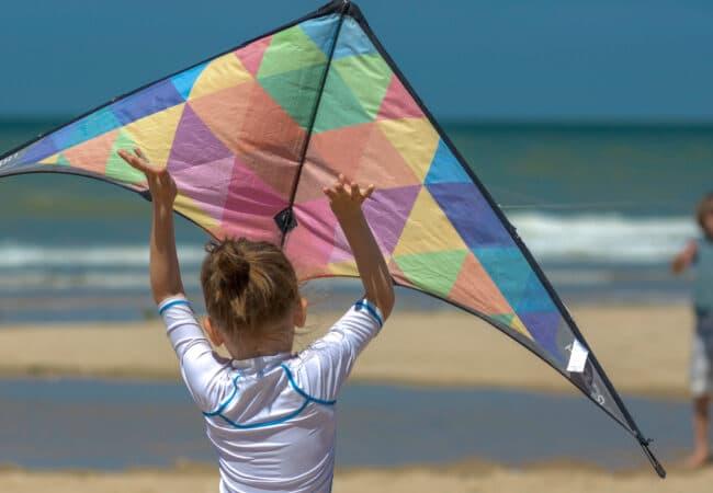 Deux enfants font du cerf volant sur la plage