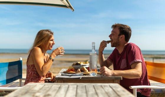 couple mangeant devant une plage