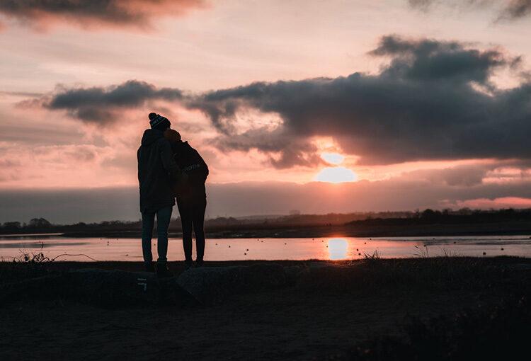 Couple regardant le coucher de soleil à la plage